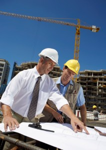 Men in Hard Hats on a Building Site Discuss a Blueprint