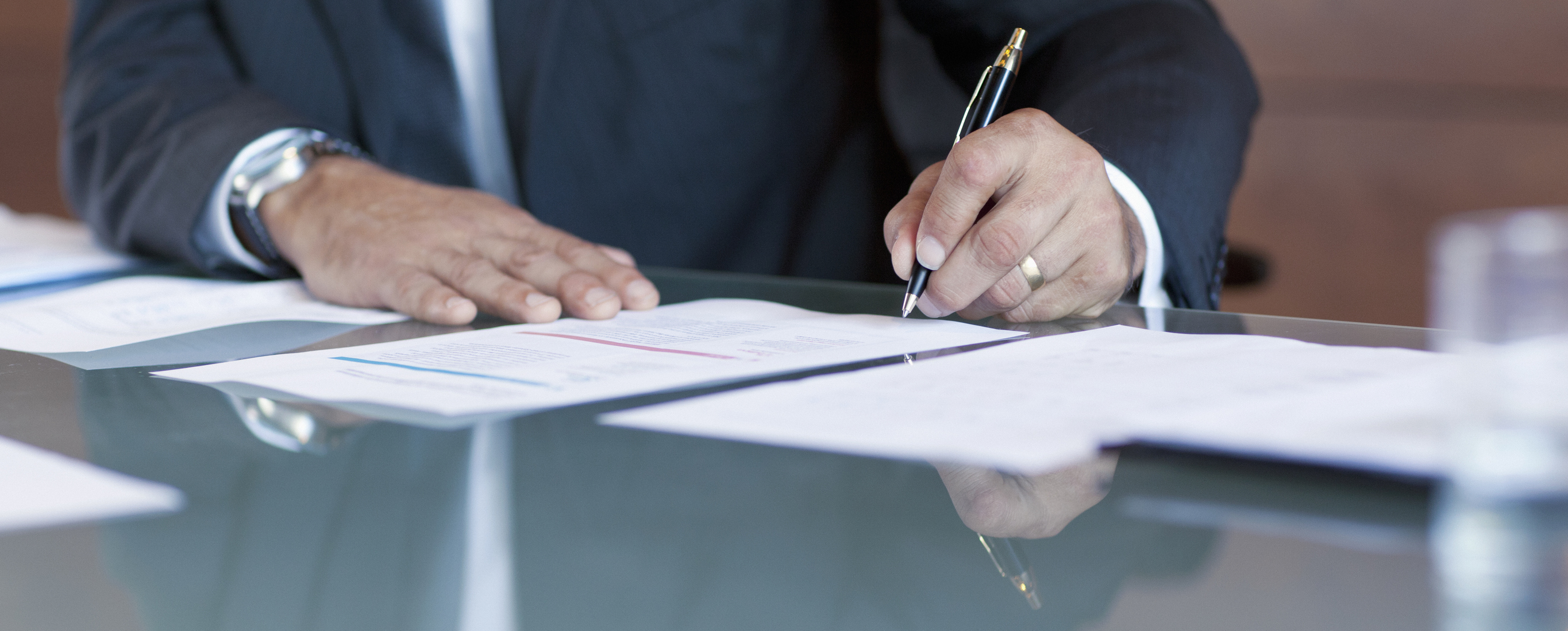 Businessman signing contract at table