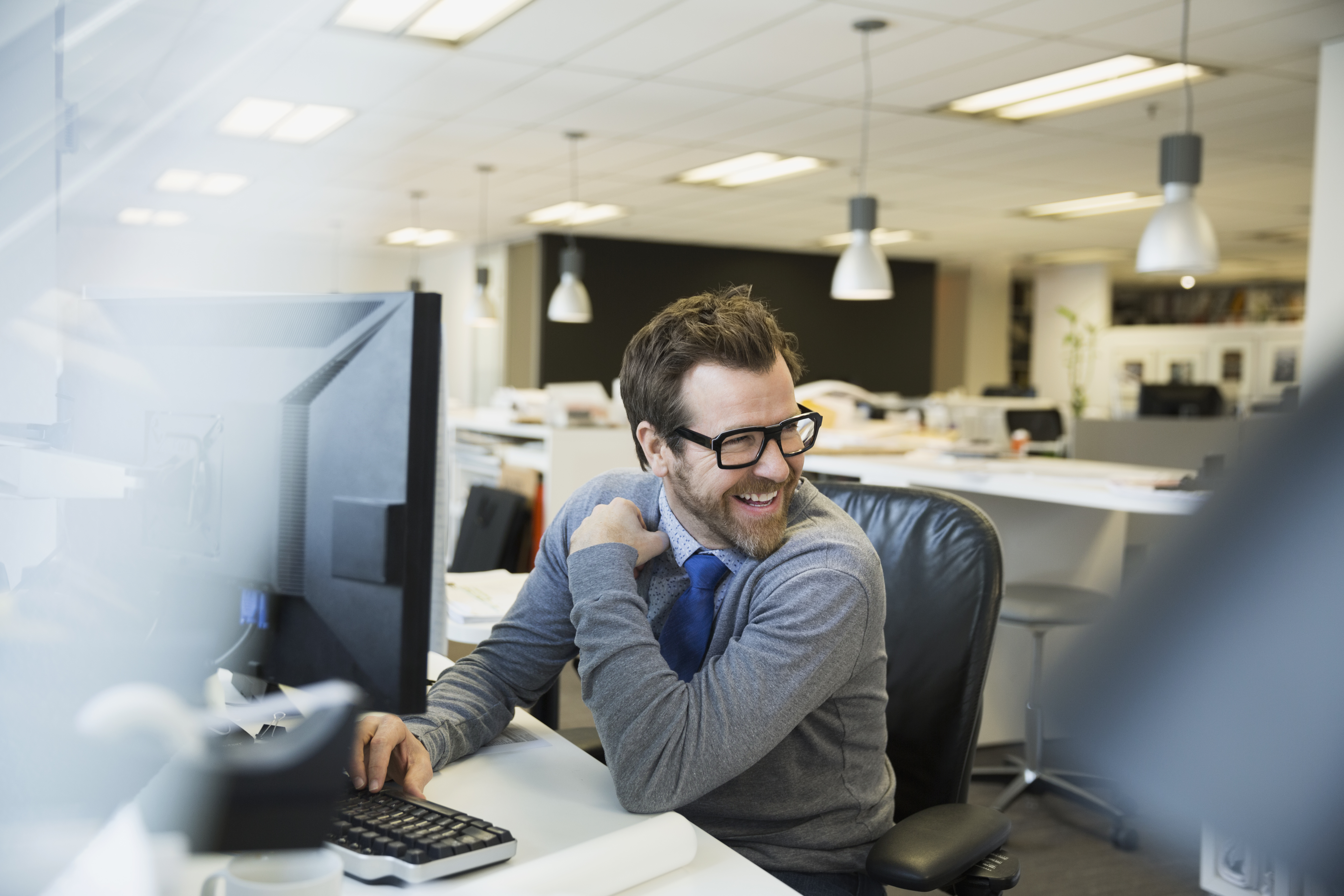 Smiling businessman working at computer looking over shoulder