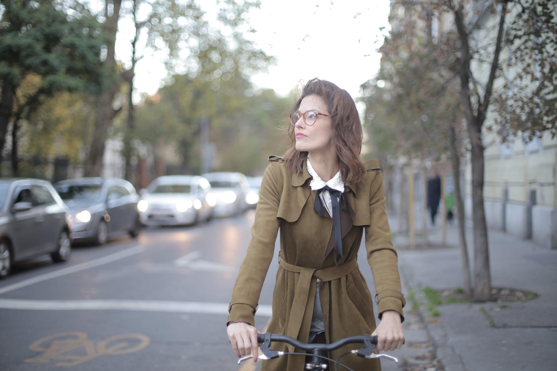 black bicycle driven by a woman wearing brown coat